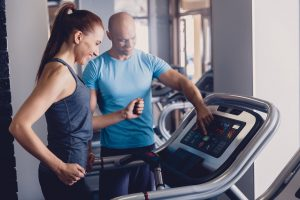 running coach working with client on treadmill