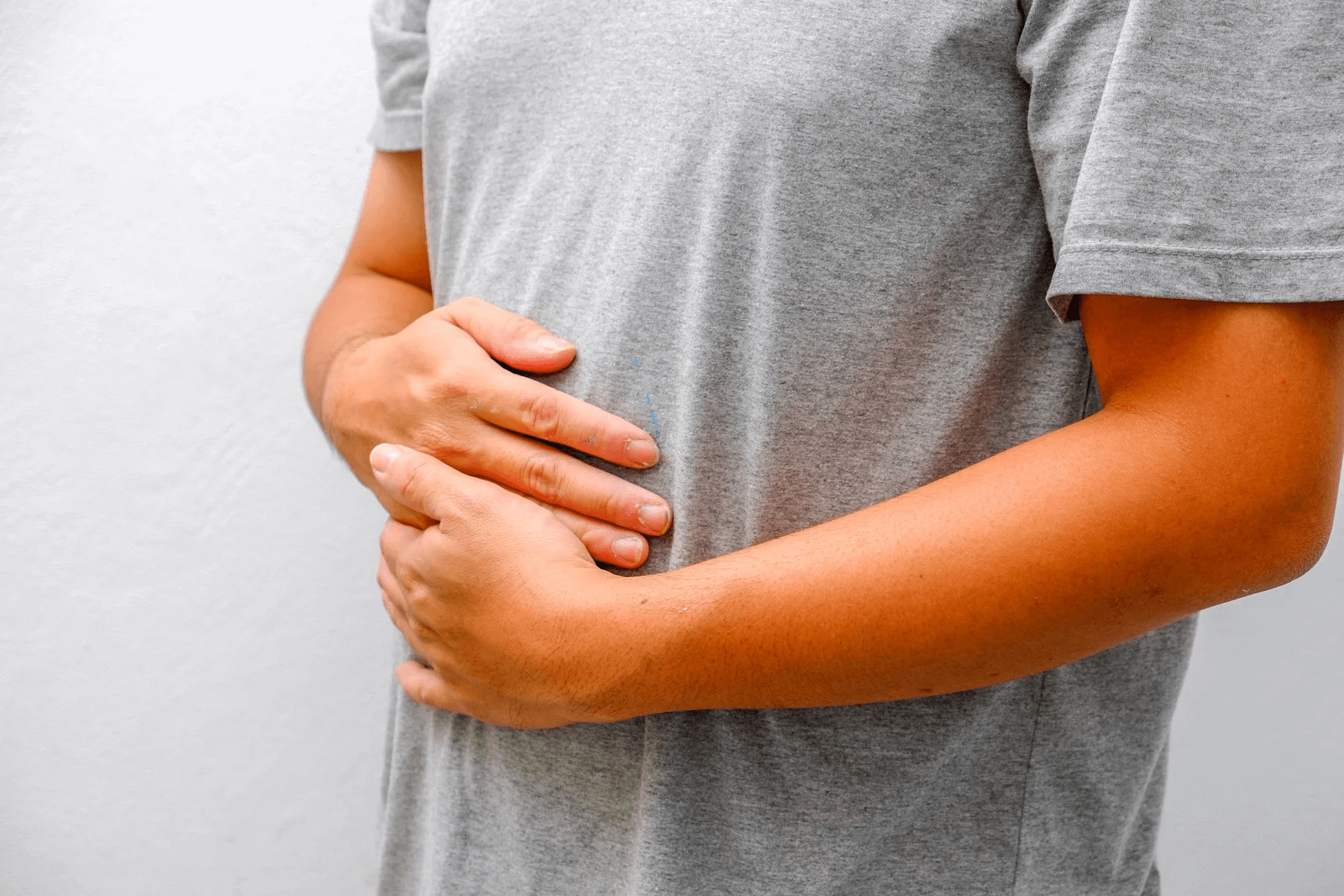 person holding stomach in pain due to gastrointestinal nutrition issues