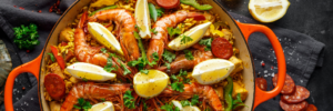 chicken and seafood paella with lemon wedges
