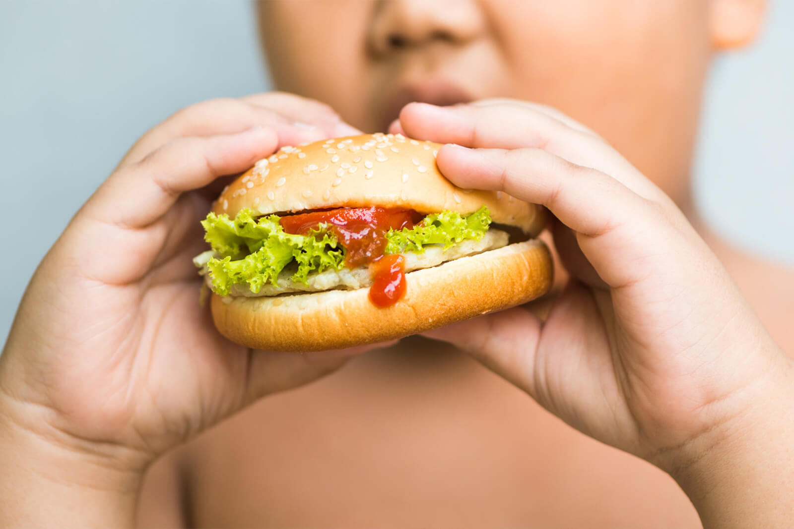 overweight child holding a burger displaying victim of overnutrition