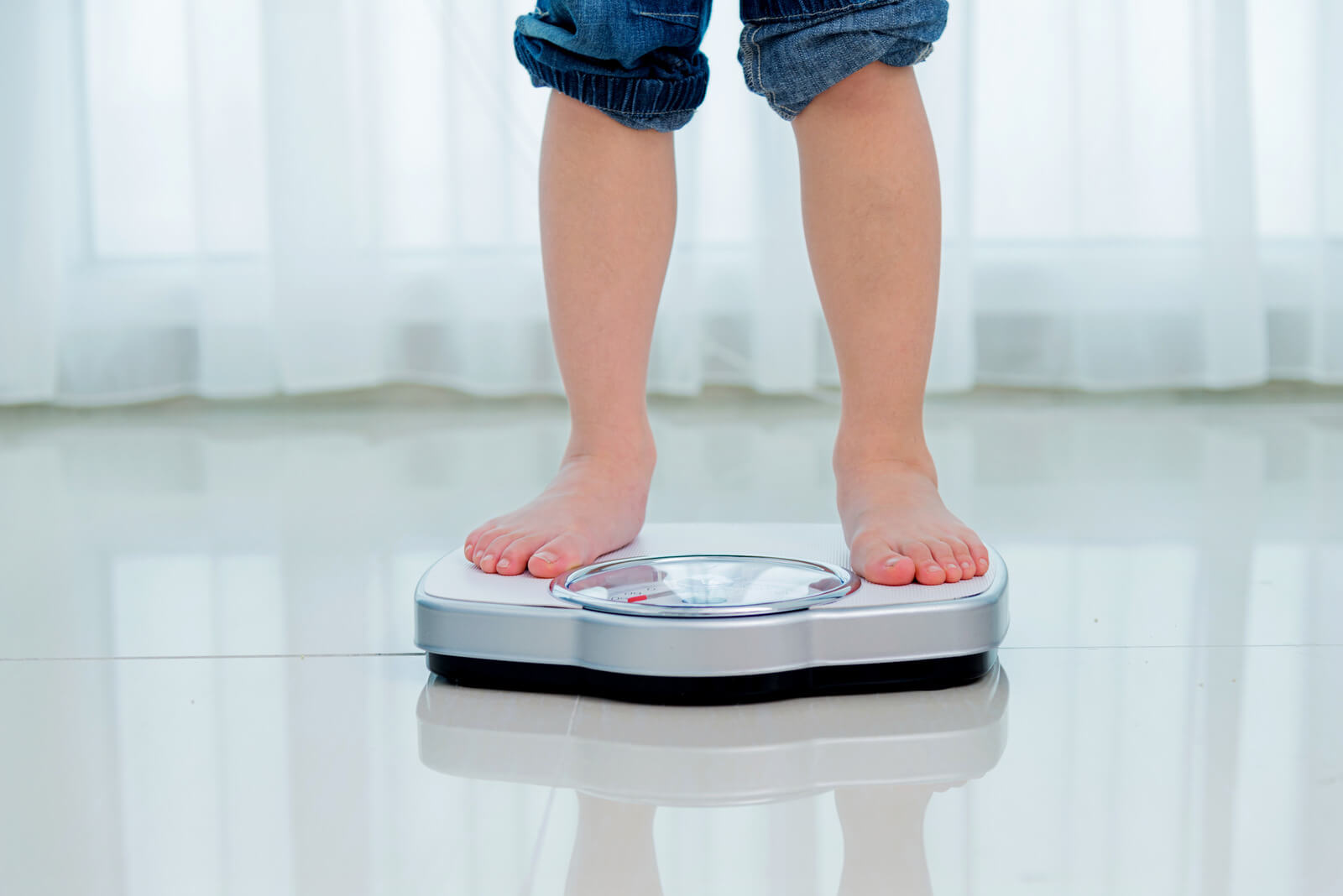 malnourished child on pediatric weight scale