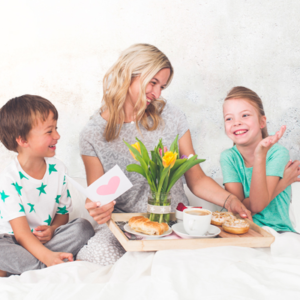 kids surprising their mother with healthy creative breakfast in bed