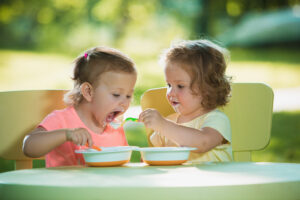 two year old kids feeding each other nutritious food